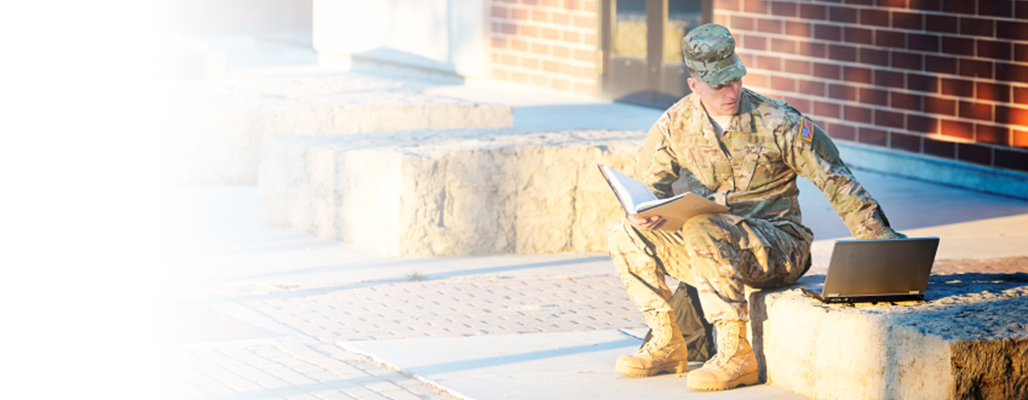 Male student on a laptop in fatigues